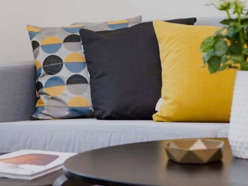home-staging-trends-couch-with-yellow-grey-pillows